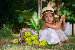 Girl in a hat and a basket of apples Royalty Free Stock Photo