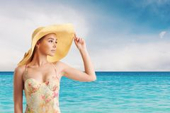 Girl with hat at the beach with a bright sea Royalty Free Stock Images