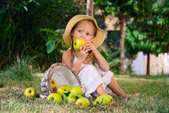 Girl in a hat biting an apple Stock Images
