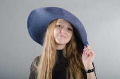Girl in a hat and a black dress Stock Photos