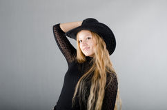 Girl in a hat and a black dress. Beautiful young girl in a hat and a black dress Royalty Free Stock Image