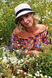 Girl in a hat, blonde woman in a hat. Summer. field of flowers, the girl in a hat in a field of flowers Stock Photography