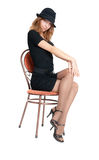 Girl in a hat on a chair Royalty Free Stock Image