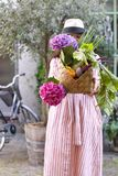 A girl in a hat on a city street with a big basket of vegetables and flowers in her hands. Beautiful woman with shopping and a royalty free stock photo