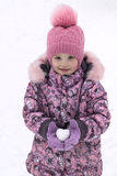 Girl in hat, coat and mittens holding a snowball in the shape of a heart. Royalty Free Stock Image