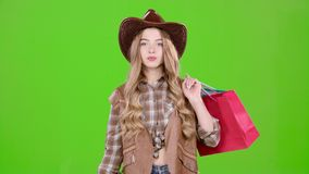 Girl in a hat and cowboy boots comes with bags in her hands. Green screen. Girl in a hat and cowboy boots comes with bags in her hands, she loves discounts in stock video