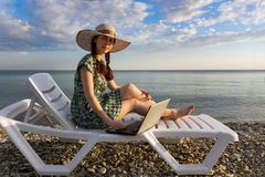 Girl in a hat and dress, on a chaise longue working at the computer, freelance, against the sea royalty free stock photos