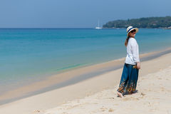 Girl in a hat and dress walking on the beach in Thailand. Royalty Free Stock Photography