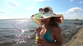 The girl in the hat drinks juice by the water. A young woman in a cap drinks orange juice on a beach by the river stock footage