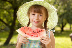 Girl in hat eating a watermelon Royalty Free Stock Image