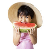 Girl with hat eats watermelon in studio Stock Photography