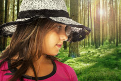 Girl with a hat with a forest on backgroung royalty free stock photography