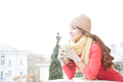 The girl in the hat froze and drinking hot tea Royalty Free Stock Photos