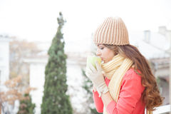 The girl in the hat froze and drinking hot tea Stock Photography