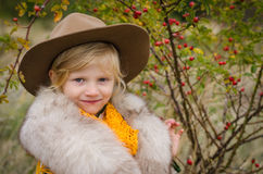 Girl with hat and fur pelerine in autumn field with rose-hips Stock Images