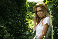 A girl in a hat with a gaze. Girl in a hat on a green background of greenery Royalty Free Stock Photos