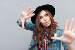 Girl in hat gesturing with hands and looking at camera. Close up portrait of a casual cute girl in hat gesturing with hands and looking at camera isolated over Stock Images