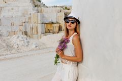 Girl in hat and glasses with a bouquet of lilac flowers near the marble white wall royalty free stock images