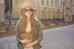 Girl in hat and glasses holding book stock images