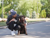 A girl hugs her dog while squatting a dog stock photos