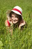 Girl in hat on green field Stock Images