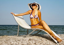 The girl in a hat having a rest on seacoast Stock Photo