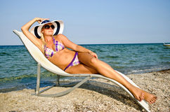 The girl in a hat having a rest on seacoast Royalty Free Stock Photography