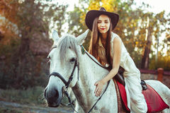 The girl in the hat on the horse. Young cowgirl on white horse smile in hat Royalty Free Stock Image