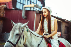 The girl in the hat on the horse. Young cowgirl on white horse smile Royalty Free Stock Photo