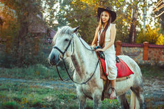 The girl in the hat on the horse. Young cowgirl on white horse smile in hat Stock Image