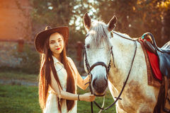 The girl in the hat on the horse. Young cowgirl on white horse smile in hat Royalty Free Stock Photos