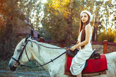 The girl in the hat on the horse. Young cowgirl on white horse smile Royalty Free Stock Images