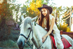 The girl in the hat on the horse. Young cowgirl on white horse smile in hat Royalty Free Stock Photography