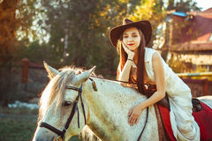 The girl in the hat on the horse. Young cowgirl on white horse smile in hat Stock Photos