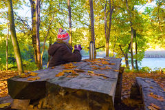 The girl in hat and jacket is sitting at the wooden table. Royalty Free Stock Photos