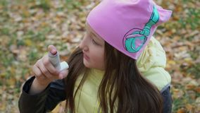 A girl in a hat and jacket takes medicine in the form of an inhaler for bronchial asthma in the autumn forest during a walk. Flu s