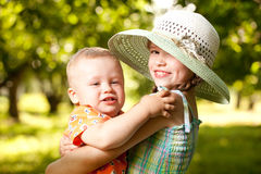 Girl in the hat keeps the arms of his  brother Stock Photos