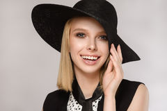 Girl in hat keeps hand near the face laughs smiles. Beautiful blondein hat keeps hand near the face laughs and smiles on the gray background. Concept of the Stock Images