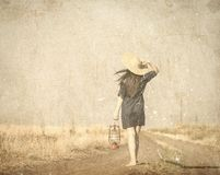 Girl in hat with lamp waking on the contryside road. Image in old color style Royalty Free Stock Image