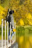 Girl in a hat with leaves in hands standing on the dock. Autumn, stock image