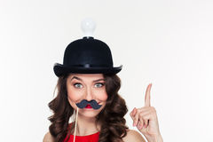 Girl in hat with light bulb using fake moustache props Royalty Free Stock Photography
