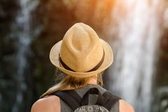 Girl in a hat looking at a waterfall. View from the back Stock Images