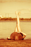 Girl in hat lying on beach. Legs raised up. Royalty Free Stock Photos