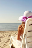 Girl in hat is lying on a deck chair on the beach Stock Images