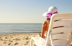 Girl in hat is lying on a deck chair on the beach Royalty Free Stock Image
