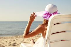 Girl in hat is lying on a deck chair on the beach Royalty Free Stock Photography