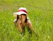 Girl in hat lying at meadow Stock Image