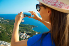 Girl in hat making photos of the Adriatic sea by the smartphone Royalty Free Stock Photo