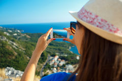 Girl in hat making photos of the Adriatic sea by the smartphone Stock Photography