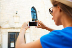 Girl in hat making photos of a church by the smartphone Stock Photography